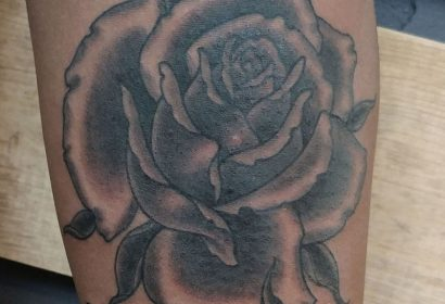 black and grey traditional style rose stem tattoo featured