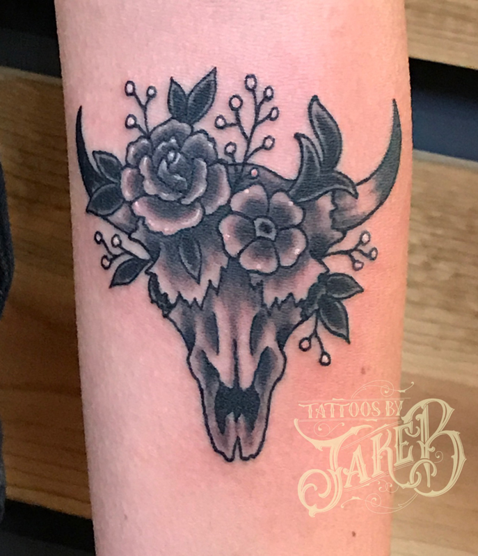 Black and grey flowers and cow skull tattoo